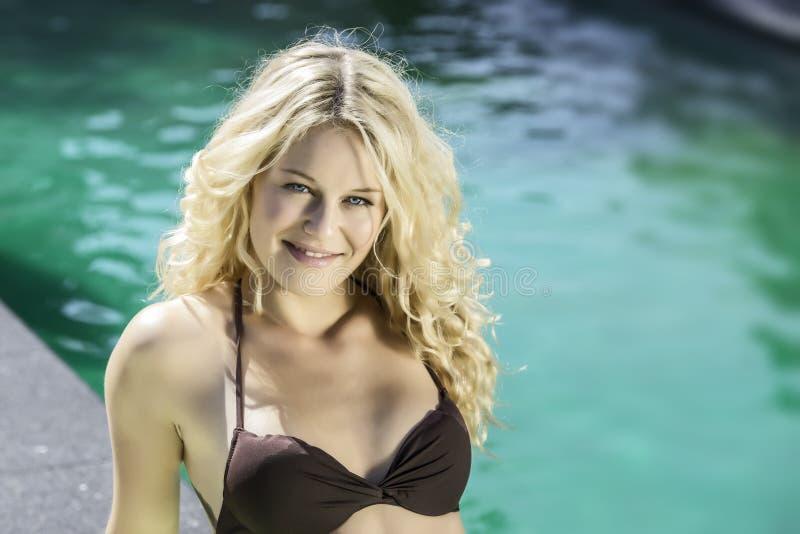 Szczęśliwy blond dziewczyny lying on the beach na basenie obraz stock