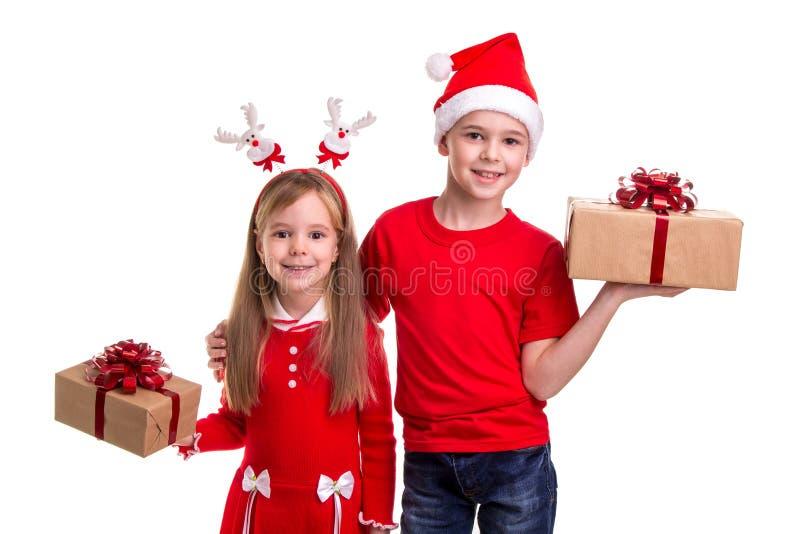 Szczęśliwy brat z Santa kapeluszem na jego głowie i siostrze z jelenimi rogami, trzyma prezentów pudełka w ich rękach Pojęcie obrazy stock