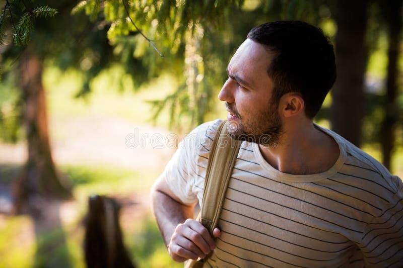 Szczęśliwy brodaty mężczyzna podróżnik z plecaka odprowadzeniem w lasowej turystyce, podróż, przygoda, podwyżki pojęcie - uśmiech zdjęcie royalty free