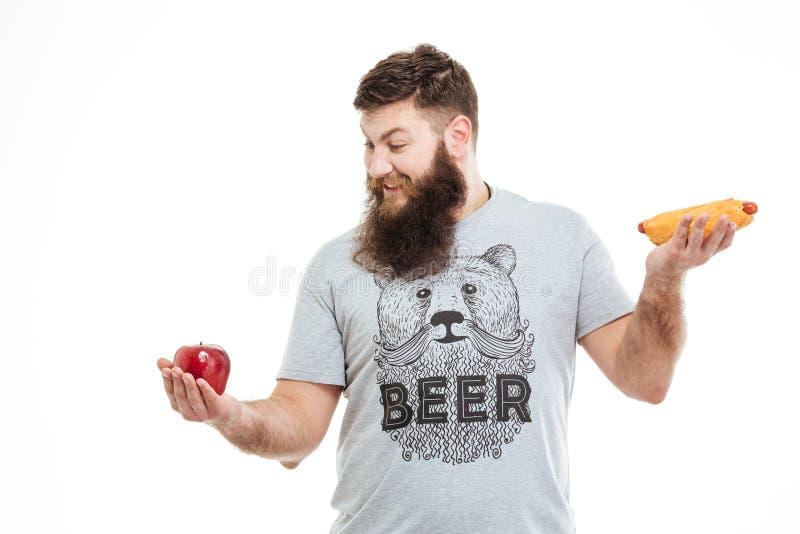 Szczęśliwy brodaty mężczyzna wybiera między czerwonym jabłkiem i hot dog fotografia royalty free