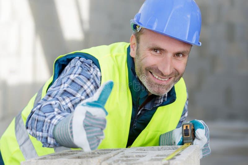 Szczęśliwy budowniczego mężczyzna śmia się aprobaty i robi przy kamerą obraz royalty free