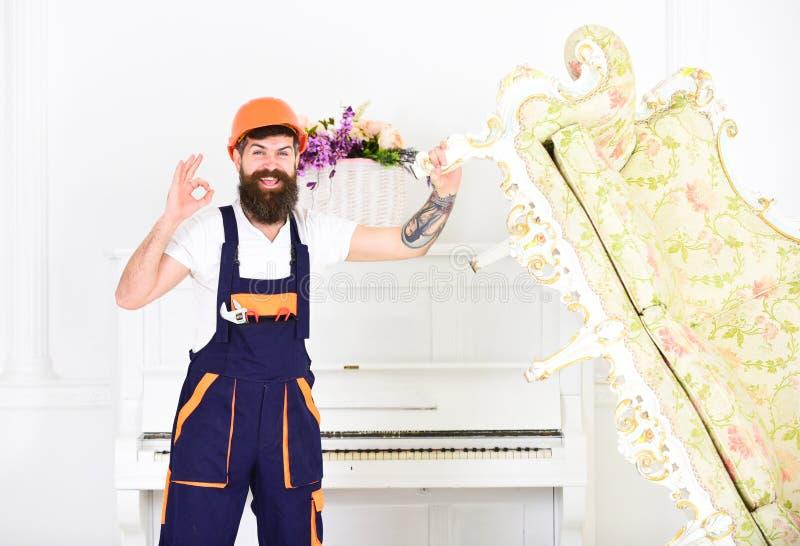 Szczęśliwy budowniczy przenosi rocznik kanapę przed odmalowywaniem Uśmiechnięta wnioskodawca z elegancką brodą i wąsy pokazuje ok obrazy stock