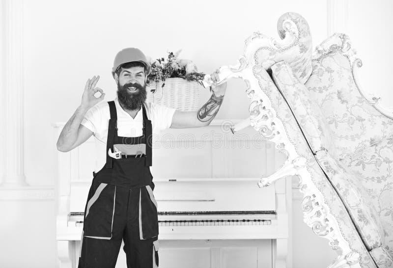 Szczęśliwy budowniczy przenosi rocznik kanapę przed odmalowywaniem Uśmiechnięta wnioskodawca z elegancką brodą i wąsy pokazuje ok zdjęcie royalty free
