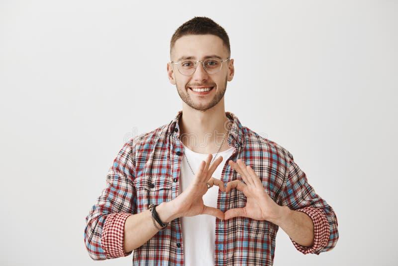 Szczęśliwy być w miłości z tobą Studio strzał atrakcyjny zwyczajny facet w szkłach pokazuje serce podpisuje klatkę piersiową, ono obraz royalty free