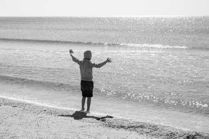 Szczęśliwy chłopiec bieg, doskakiwanie w fala na czarnym morzu i wyrzucać na brzeg fotografia stock