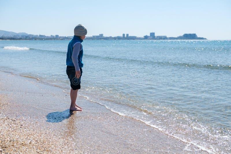 Szczęśliwy chłopiec bieg, doskakiwanie w fala na czarnym morzu i wyrzucać na brzeg obraz stock