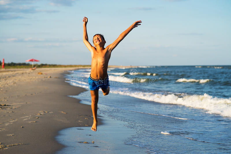 Szczęśliwy chłopiec bieg na dennej plaży przy latem obraz royalty free