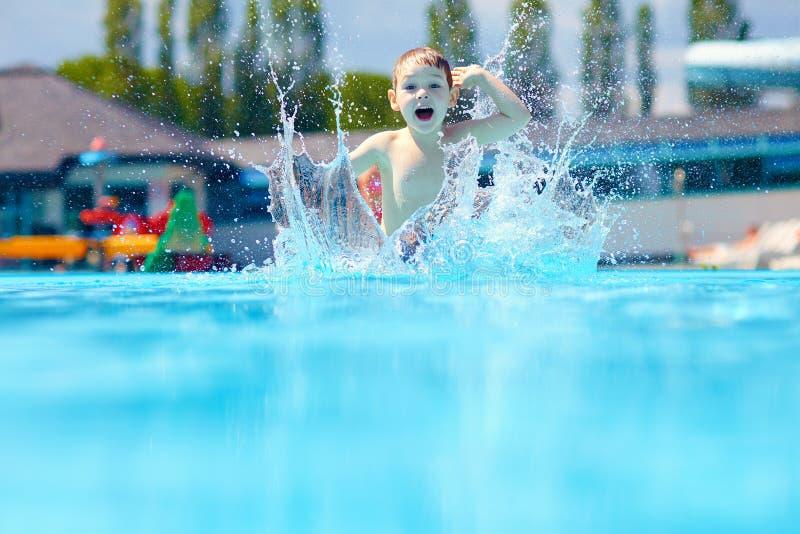 Szczęśliwy chłopiec dzieciaka doskakiwanie w basenie zdjęcie royalty free