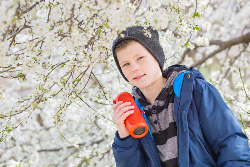 Szczęśliwy chłopiec nastolatek z przenośnym bezprzewodowym głośnikowym słuchaniem muzyka fotografia stock