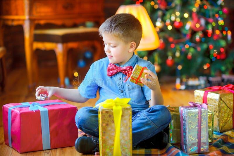 szczęśliwy chłopiec obsiadanie na mieniu i podłodze jego teraźniejszość na tle światła świąteczna choinka, boże narodzenia obraz royalty free