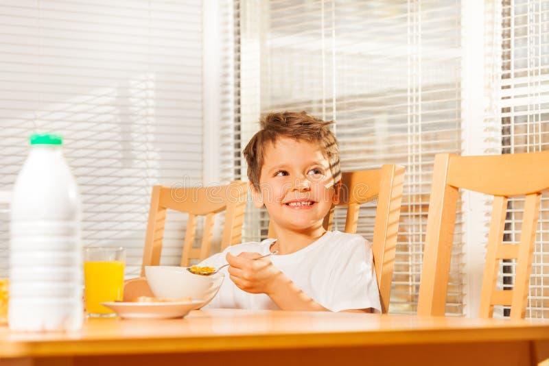 Szczęśliwy chłopiec obsiadanie przy śniadaniowego łasowania kukurydzanymi płatkami fotografia stock