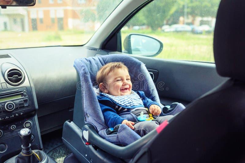 Szcz??liwy ch?opiec obsiadanie w samochodzie w zbawczym krze?le fotografia stock