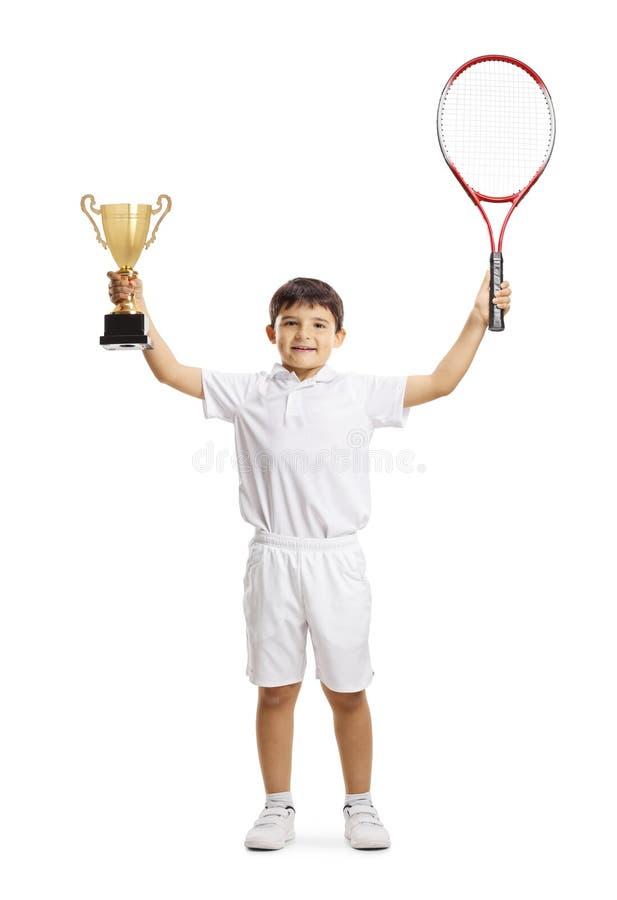 Szczęśliwy chłopiec zwycięzca w młodzieżowym tenisie z trofeum filiżanką obraz stock