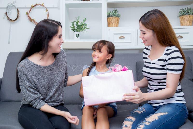 Szczęśliwy ciocia z prezentem z różową całowanie matką i azjata matki i córki obraz stock