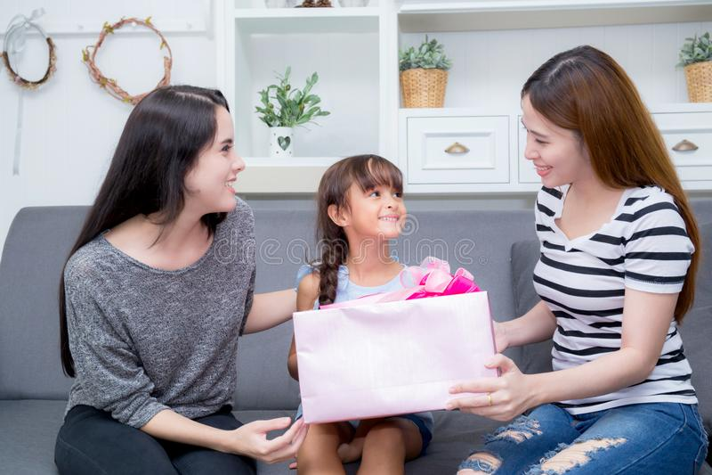 Szczęśliwy ciocia z prezentem z różową całowanie matką i azjata matki i córki obrazy stock