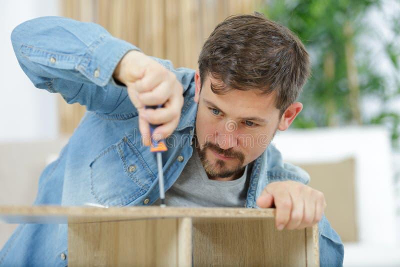 Szczęśliwy człowiek wkręca śruby w wyposażenie mebli fotografia stock