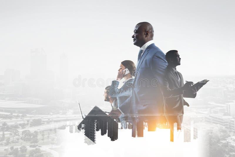 Szczęśliwy czarny biznesmen z innymi ludźmi pracuje w biurze na pejzażu miejskiego tle fotografia royalty free