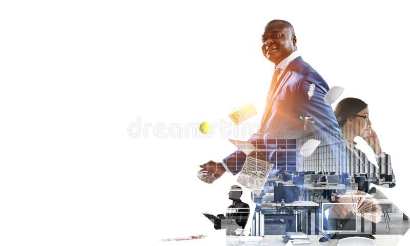 Szczęśliwy czarny biznesmen z innymi ludźmi pracuje w biurze obraz stock