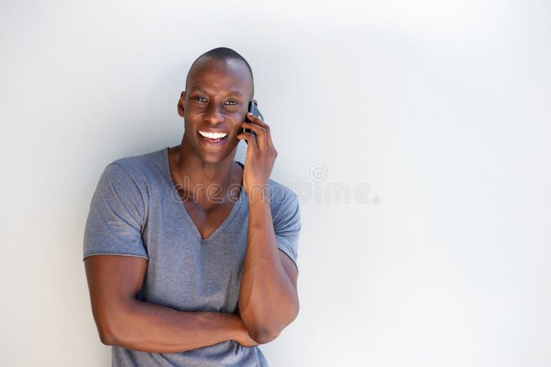 Szczęśliwy czarny facet opiera przeciw bielu ścienny opowiadać na telefonie komórkowym obraz stock