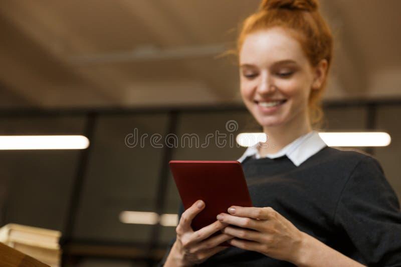 Szczęśliwy czerwony z włosami nastoletniej dziewczyny studiowanie przy biblioteką zdjęcie royalty free