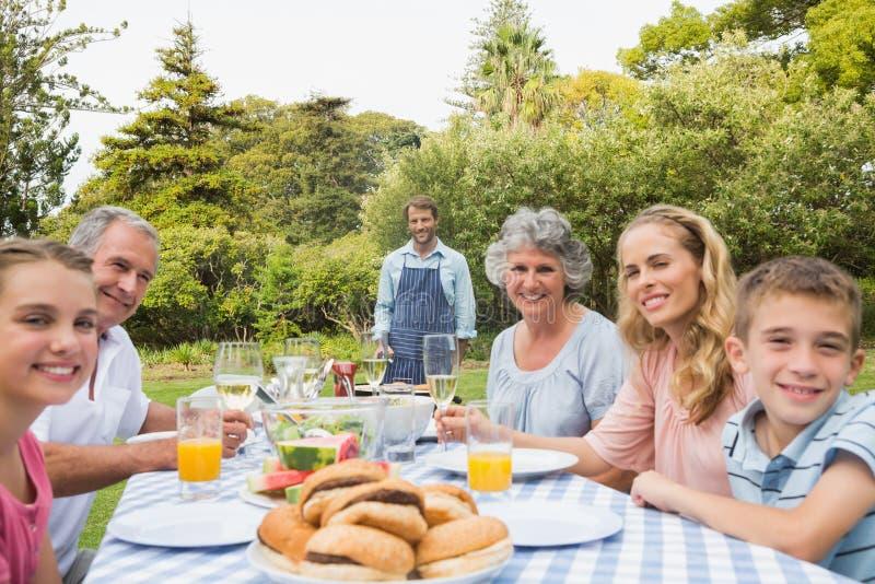 Szczęśliwy dalszej rodziny czekanie dla grilla gotuje ojcem obraz royalty free