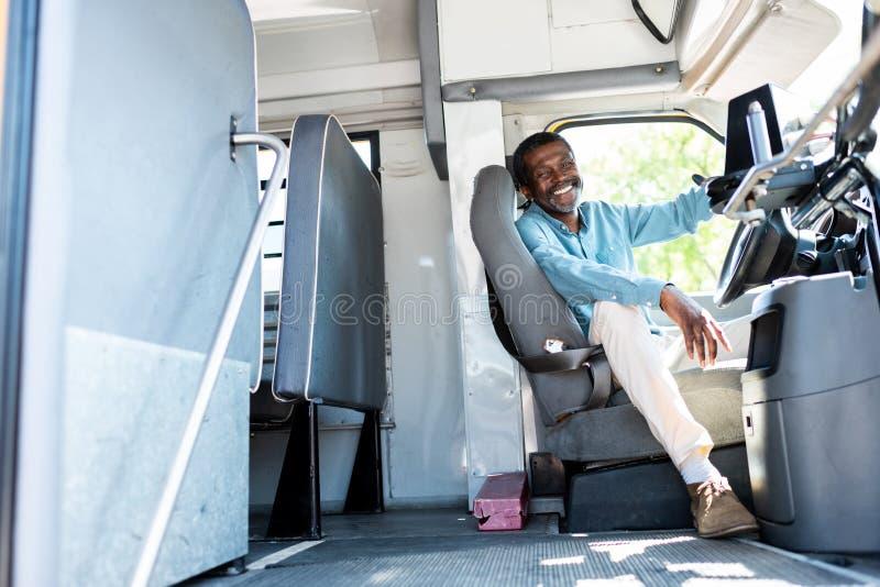 szczęśliwy dojrzały amerykanin afrykańskiego pochodzenia kierowca autobusu patrzeje kamerę podczas gdy siedzący zdjęcie royalty free