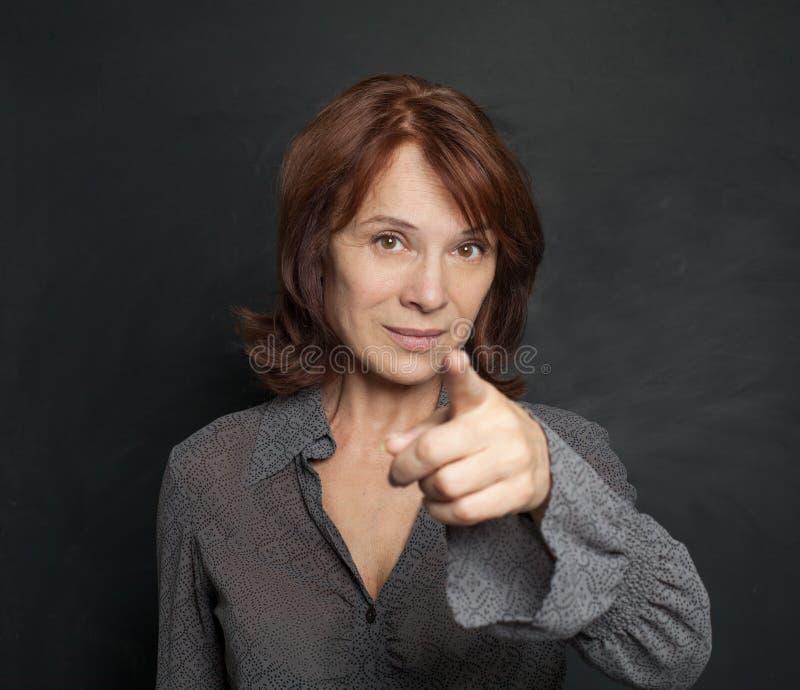 Szczęśliwy dojrzały kobieta bizneswoman wskazuje na blackboard zdjęcie royalty free