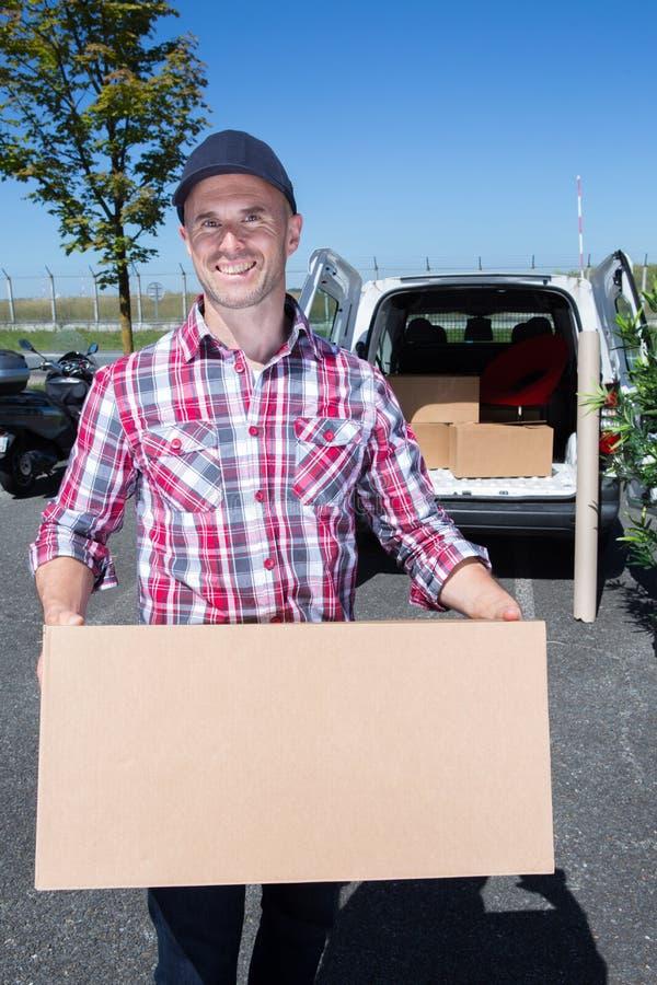 Szczęśliwy doręczeniowy mężczyzna z cardbox pozycją samochodem dostawczym obraz royalty free