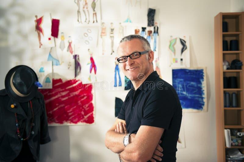Szczęśliwy dorośleć mężczyzna działanie jako projektant mody fotografia stock