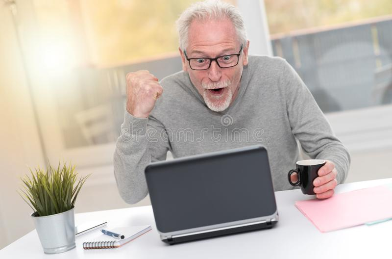 Szczęśliwy dorośleć mężczyzna ma dobrą niespodziankę na laptopie, lekki skutek zdjęcia royalty free