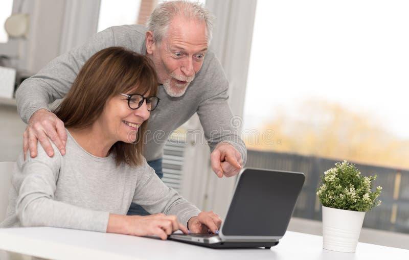 Szczęśliwy dorośleć pary ma dobrą niespodziankę na laptopie zdjęcie stock