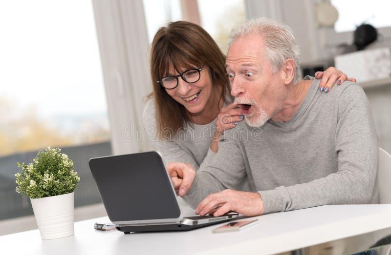 Szczęśliwy dorośleć pary ma dobrą niespodziankę na laptopie fotografia stock