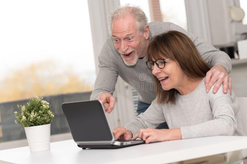 Szczęśliwy dorośleć pary ma dobrą niespodziankę na laptopie zdjęcia stock