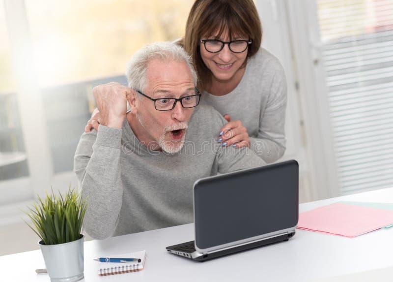 Szczęśliwy dorośleć pary ma dobrą niespodziankę na laptopie, lekki skutek zdjęcia stock