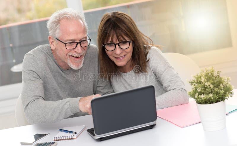 Szczęśliwy dorośleć pary ma dobrą niespodziankę na laptopie, lekki skutek obrazy royalty free