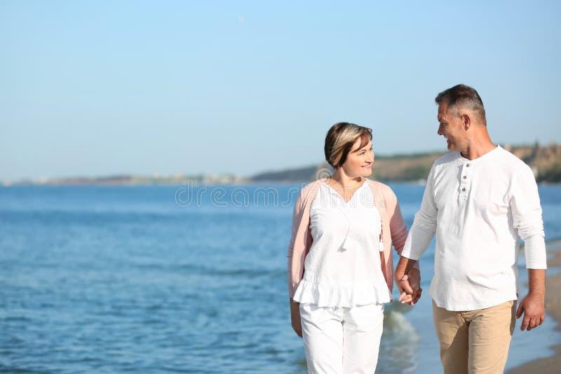 Szczęśliwy dorośleć pary odprowadzenie przy plażą obraz stock
