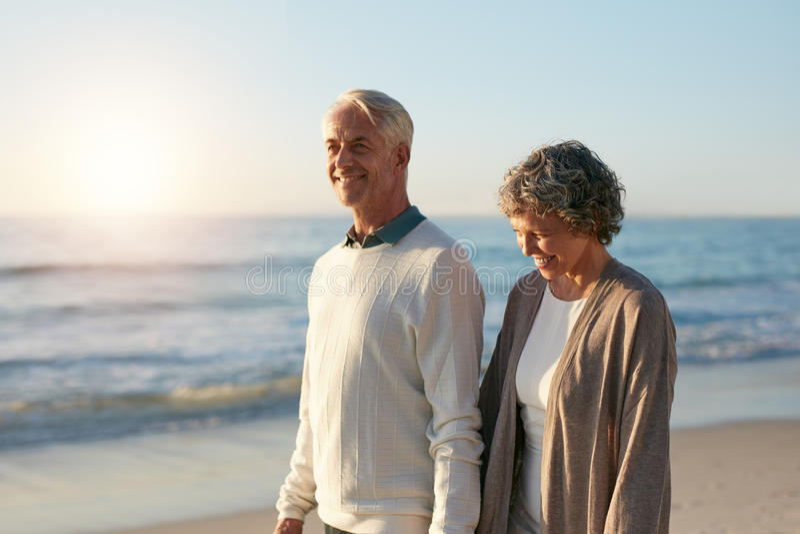 Szczęśliwy dorośleć pary odprowadzenie wzdłuż plaży obraz royalty free