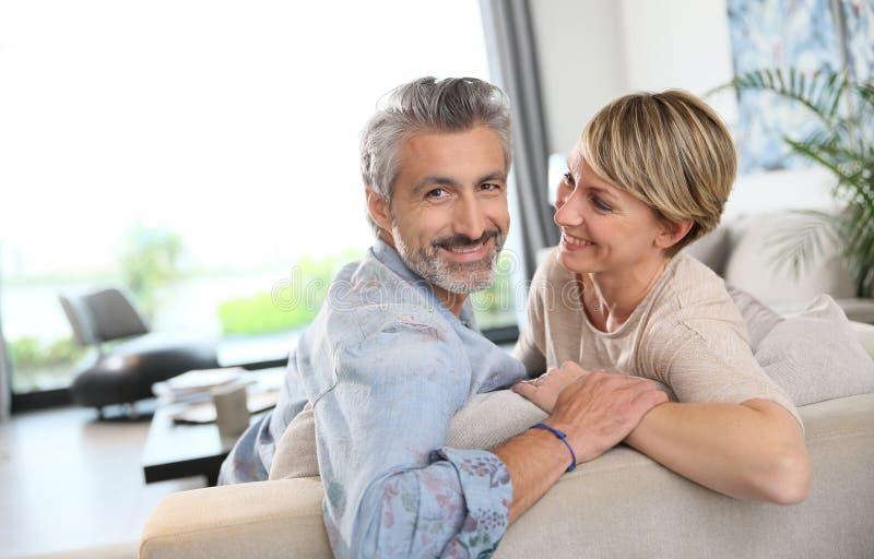 Szczęśliwy dorośleć pary relaksuje w żywym pokoju obrazy stock
