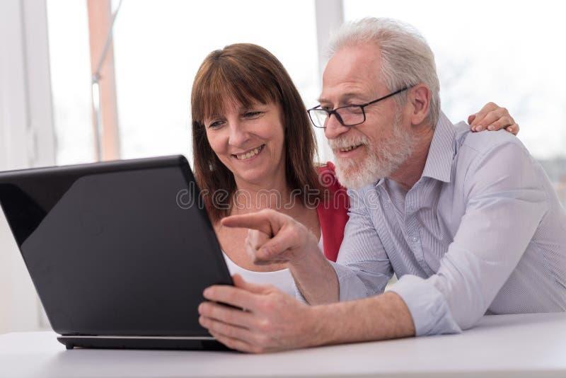 Szczęśliwy dorośleć pary używa laptop zdjęcia stock