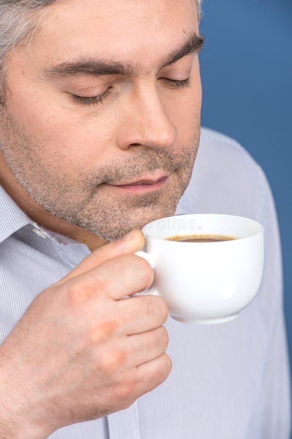 Szczęśliwy dorosły mężczyzna pije kawę na błękicie obraz stock