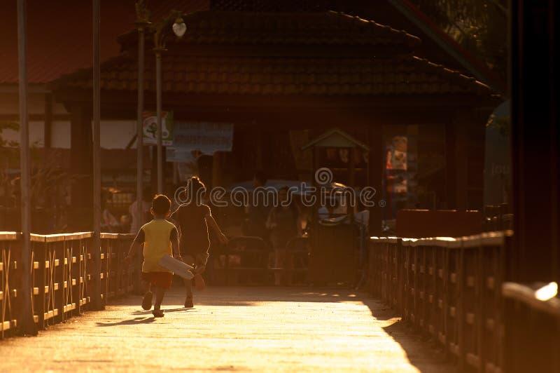 Szczęśliwy dwa dzieci sylwetki bawić się biegam w moscie na wieczór świetle zdjęcie stock