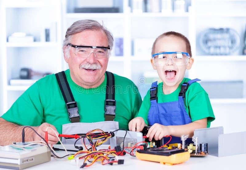 Szczęśliwy dziad i wnuk pracuje w warsztacie fotografia royalty free