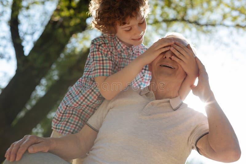 Szczęśliwy dziadek bawić się z jego wnukiem obraz royalty free