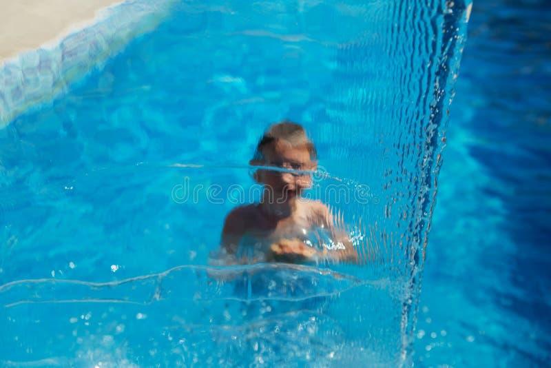 Szczęśliwy dzieciak bawić się w błękitne wody pływacki basen na tropikalnym r zdjęcia royalty free