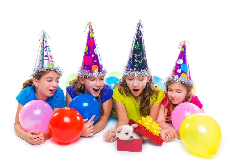 Szczęśliwy dzieciak dziewczyn szczeniaka psa prezent w przyjęciu urodzinowym obraz stock