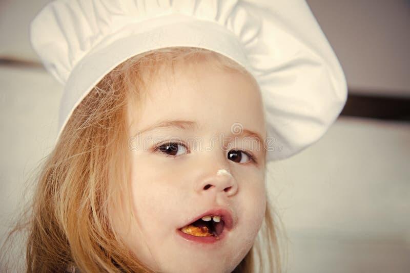 Szczęśliwy dzieciak ma zabawę Chłopiec z mąką na nosie w białym szefa kuchni kapeluszu fotografia stock