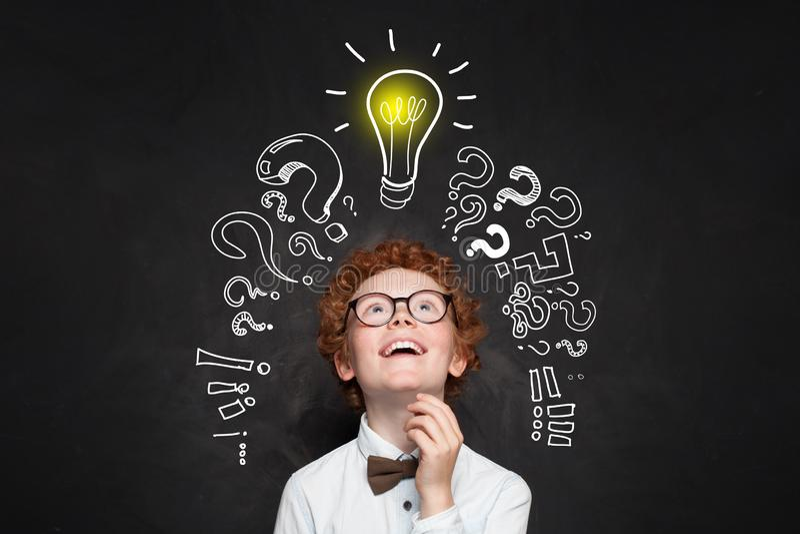 Szczęśliwy dzieciak patrzeje lightbulb na blackboard tle Brainstorming i pomys?u poj?cie obraz royalty free