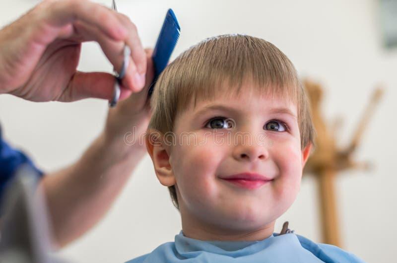 Szczęśliwy dzieciak przy fryzjerem obraz royalty free