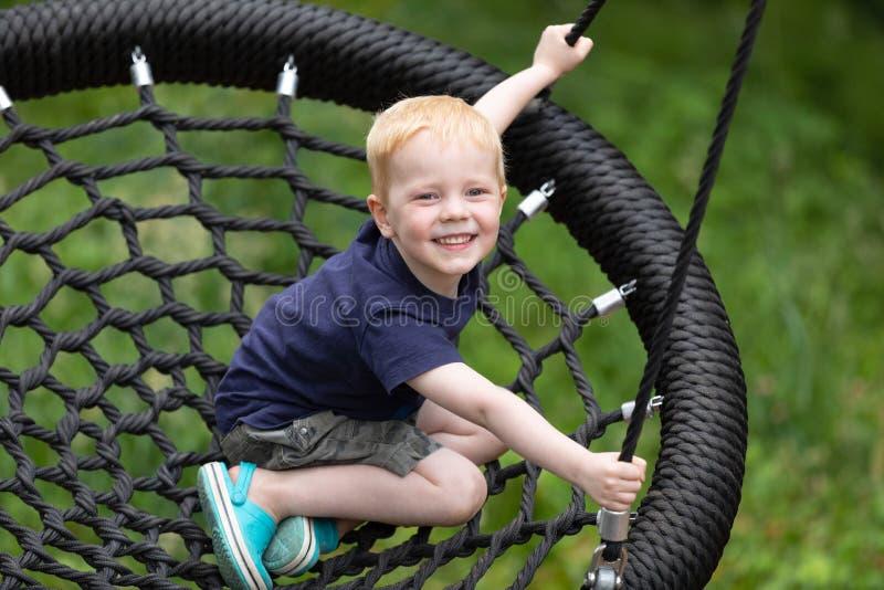 Szczęśliwy dzieciak siedzący na huśtawce obraz royalty free