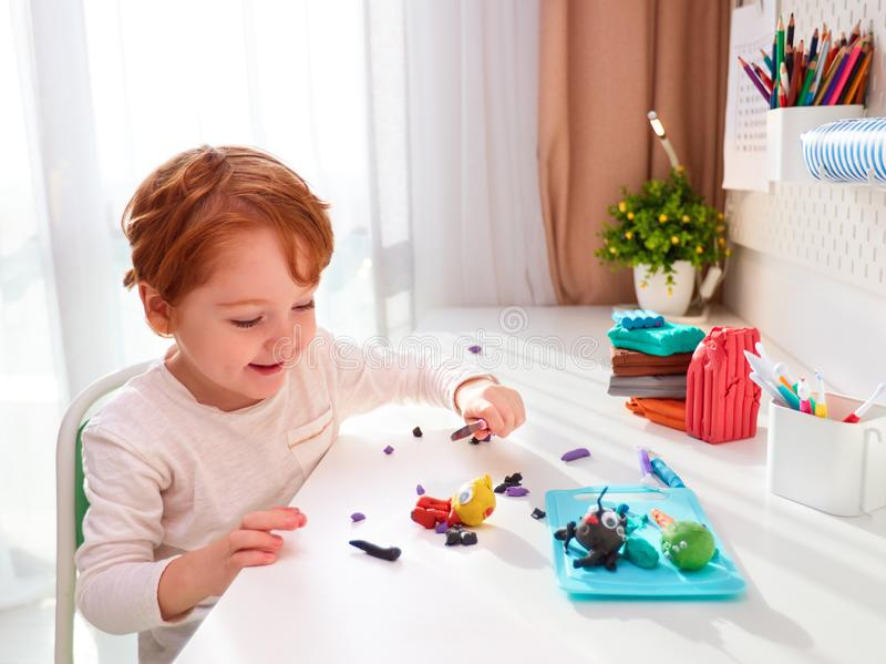 Szczęśliwy dzieciak tworzy ręczne rzemiosła z modelowania plastyny przy biurku w pokoju dla dzieci obraz royalty free